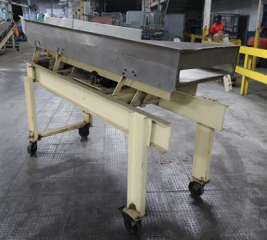 Feeder 24 w x 111 L and narrows to 12 1/2  Newcombe Enterprises vibratory feeder model Serial #581-014A1381, Stainless Steel